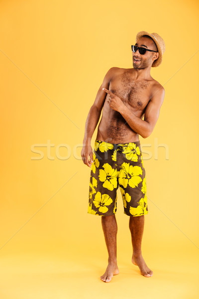 Smiling afro american man in swimwear pointing finger away Stock photo © deandrobot