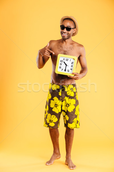 Afro american man in swimwear pointing finger at wall clock Stock photo © deandrobot