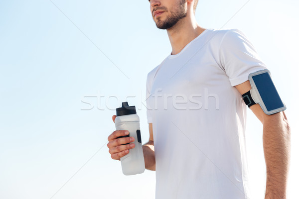 Cropped image of a male sportsman holding water bottle outdoors Stock photo © deandrobot