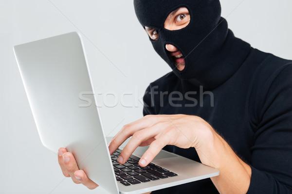 Primer plano criminal hombre usando la computadora portátil negocios máscara Foto stock © deandrobot