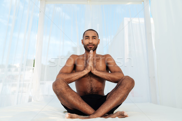 Young smiling afro american man mediating Stock photo © deandrobot