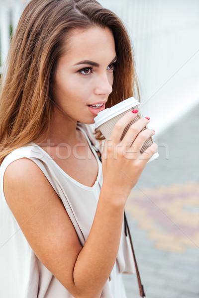 Woman drinking take away coffee while walking on the street Stock photo © deandrobot