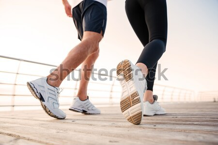 Cropped image of three runners sprinting outdoors Stock photo © deandrobot