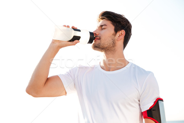 Thirsty athlete drinking water after workout Stock photo © deandrobot