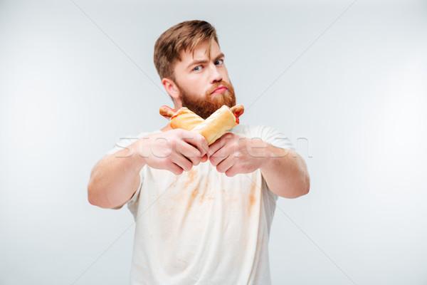 Fiatal szakállas férfi mocskos póló tart Stock fotó © deandrobot