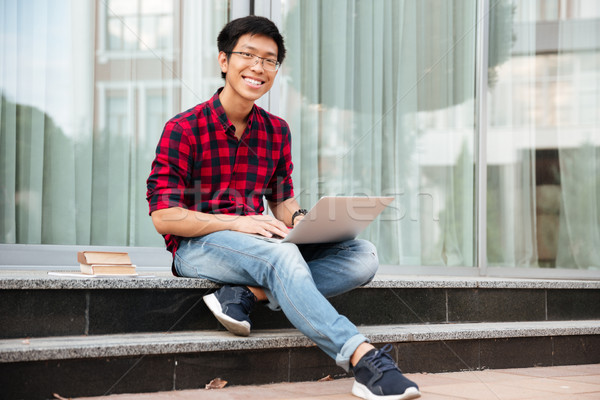 Happy asian young man using laptop outdoors Stock photo © deandrobot