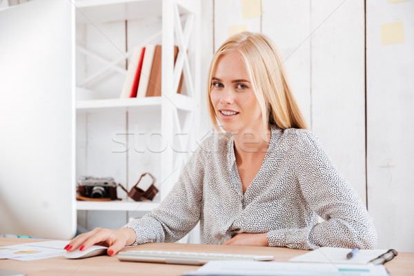 Smiling business woman sitting at workplace and using computer Stock photo © deandrobot