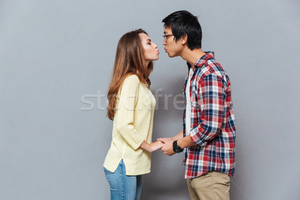 Young attractive interracial couple standing and kissing Stock photo © deandrobot