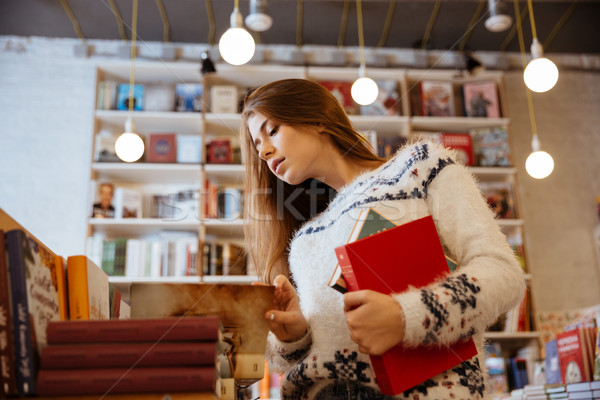 Pretty young woman choosing books in library Stock photo © deandrobot