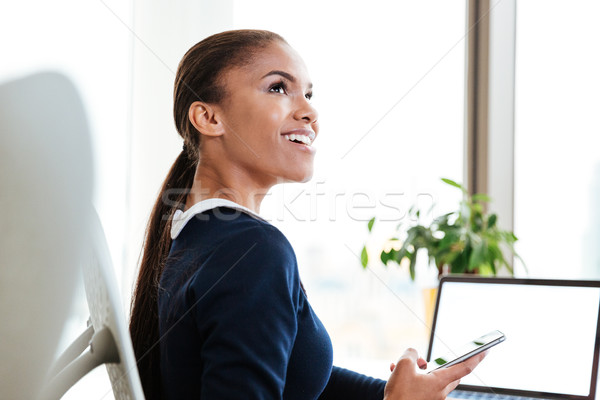 Stock photo: Happy african business woman holding phone
