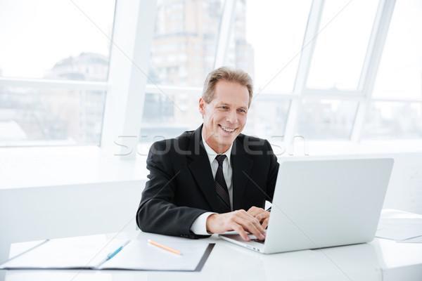 Elderly business man with laptop Stock photo © deandrobot