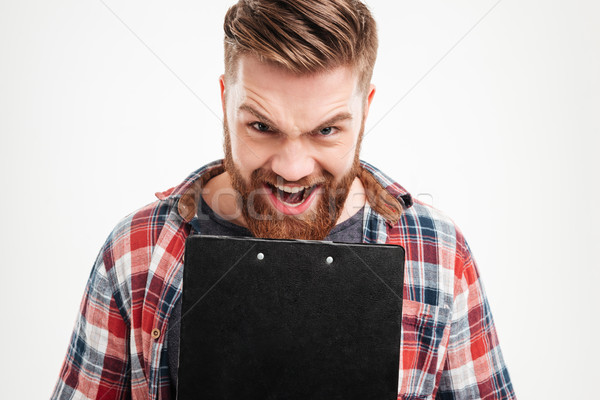 Young bearded man screaming and holding black clipboard Stock photo © deandrobot