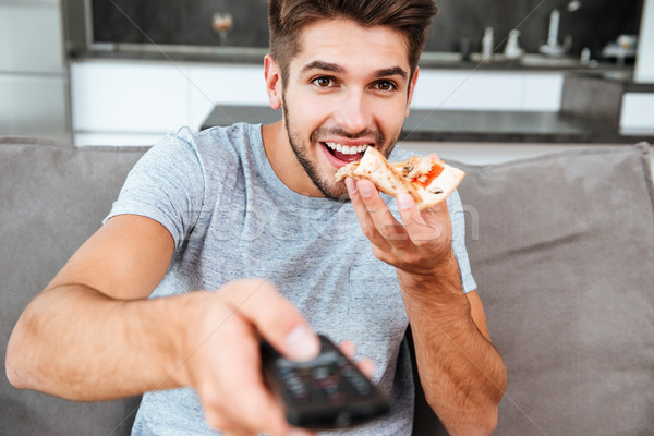 Man pushing the button on remote control while eating pizza Stock photo © deandrobot