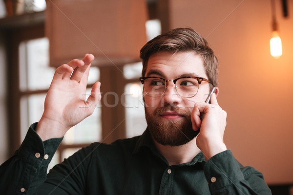 Stock photo: Young man talking by phone and waving look aside.