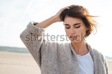 Portrait of woman in coat an the seaside in autumn Stock photo © deandrobot