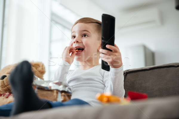 Cute boy sitting on sofa with remote control. Stock photo © deandrobot