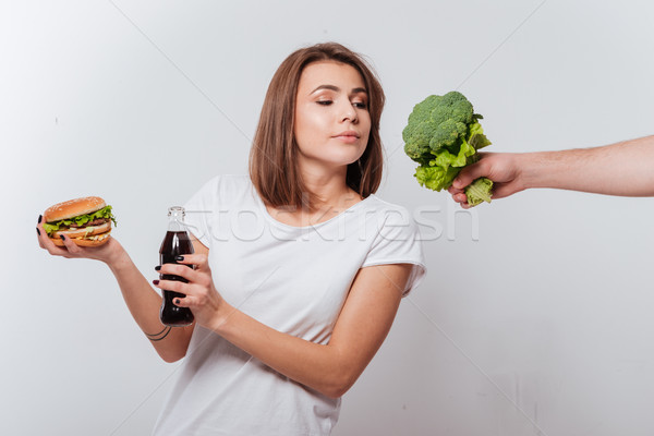 Hungry young lady holding fastfood and look at broccoli Stock photo © deandrobot