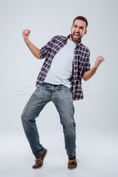 Stock photo: Vertical image of Screaming happy Bearded man in shirt