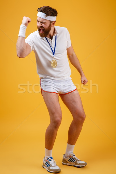 Emotional young sportsman with medal make winner gesture. Stock photo © deandrobot