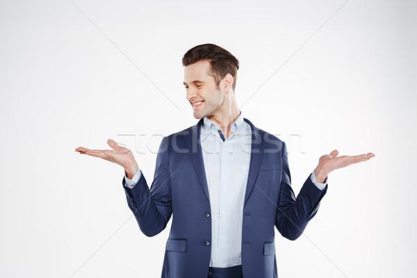 Mosolyog üzletember tart láthatatlan copy space másfelé néz Stock fotó © deandrobot