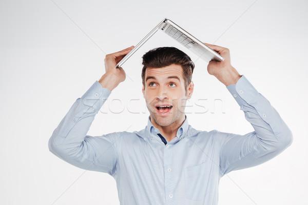 Happy business man holding laptop overhead Stock photo © deandrobot