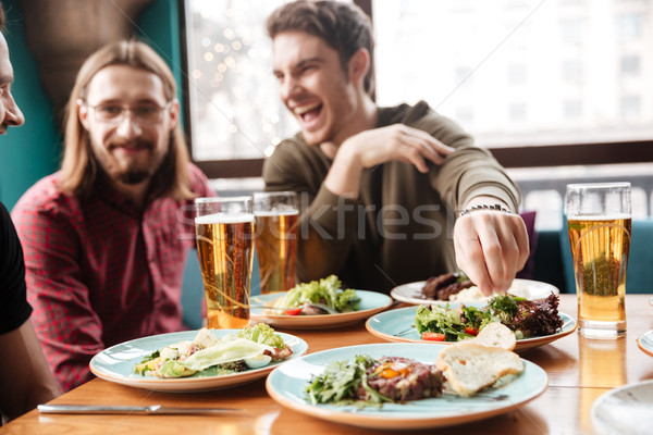 Stock photo: Young cheerful friends sitting in cafe while drinking alcohol.