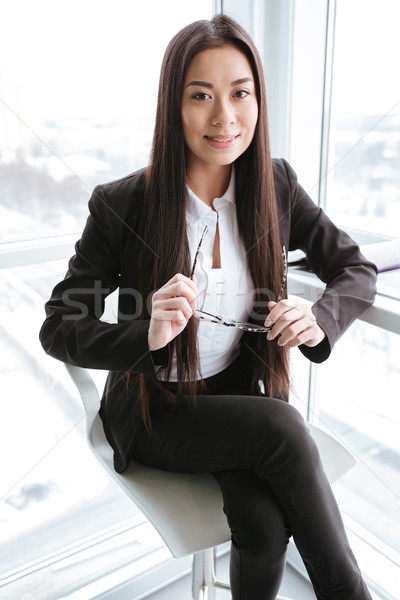 Smiling businesswoman sitting and holding her eyeglasses near the window Stock photo © deandrobot