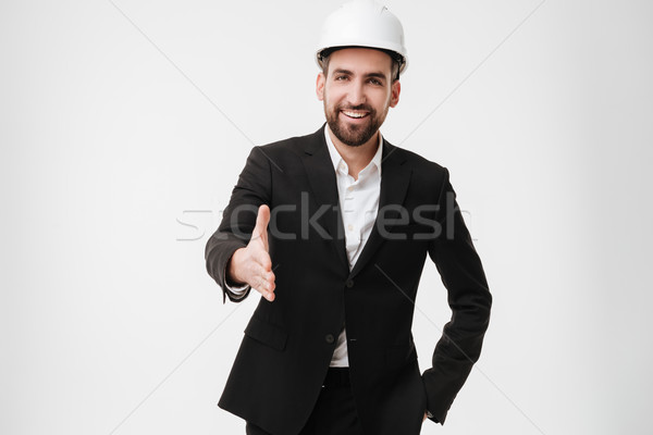 Cheerful architect wearing helmet gives a hand to camera. Stock photo © deandrobot