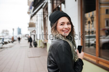 Woman in warm clothes listening music on the street Stock photo © deandrobot