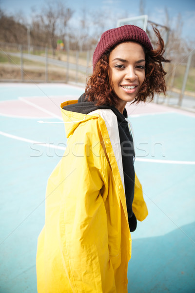 Smiling african curly young woman wearing yellow coat Stock photo © deandrobot