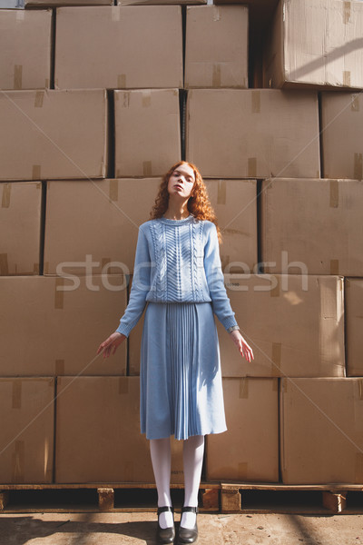 Shot of standing near boxes young woman Stock photo © deandrobot
