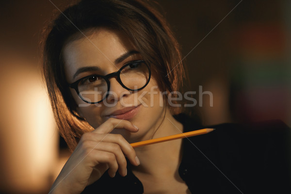 Concentrated young lady designer holding pencil. Stock photo © deandrobot