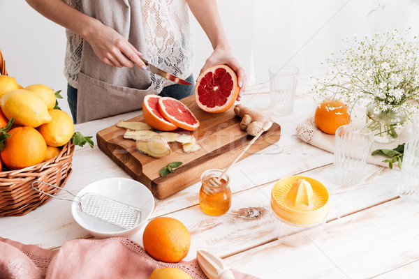 Cropped picture of young woman cut the grapefruit. Stock photo © deandrobot