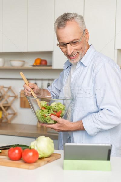 Bonito homem maduro em pé cozinha cozinhar salada Foto stock © deandrobot
