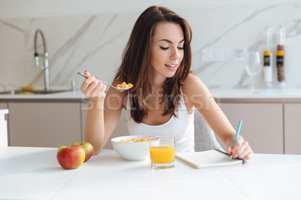 Smiling attractive woman eating corn flakes cereal for breakfast Stock photo © deandrobot