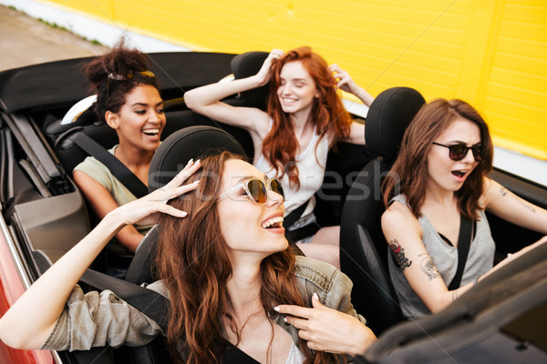 Emotional four young women friends sitting in car Stock photo © deandrobot