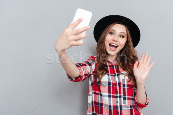 Happy young lady talking by mobile phone waving. Stock photo © deandrobot