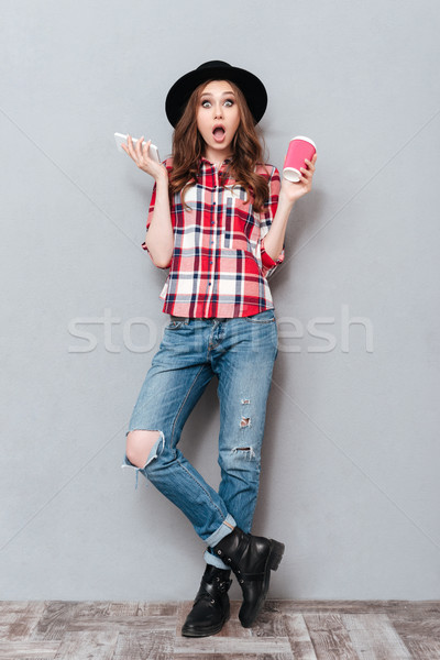 Full length portrait of a shocked girl in plaid shirt Stock photo © deandrobot
