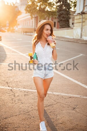Beautiful young woman with skateboard outdoors Stock photo © deandrobot