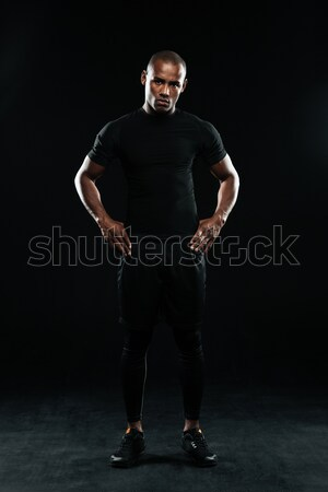 Serious afro american sports man, standing with arms on his hips Stock photo © deandrobot