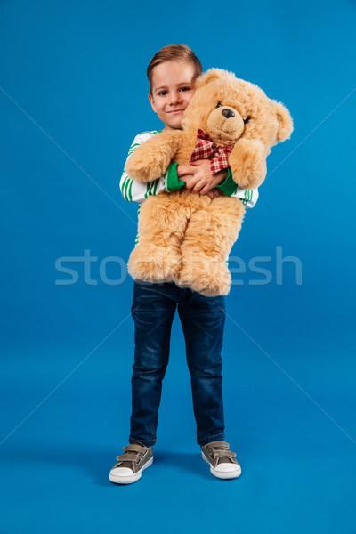 Full length portrait of a little boy hugging teddy bear Stock photo © deandrobot