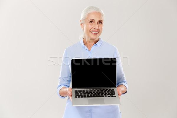 Volwassen vrouw glimlachen tonen scherm laptop geïsoleerd Stockfoto © deandrobot