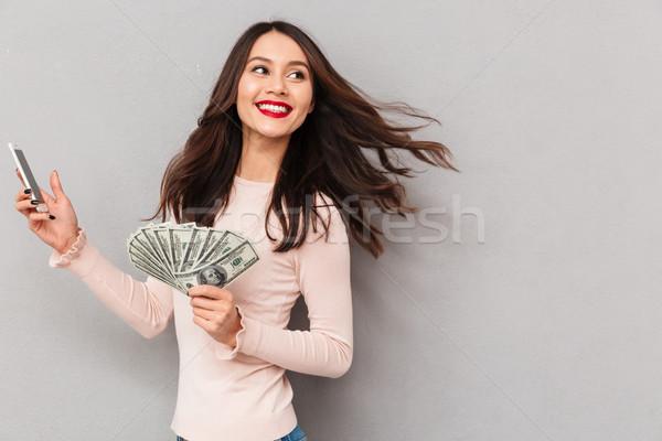 Portrait of happy brunette female 30s winning lots of money doll Stock photo © deandrobot