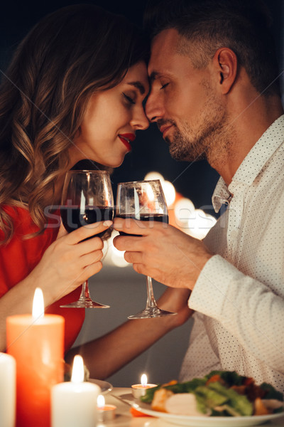 Young lady kiss her gorgeous man while have romantic dinner Stock photo © deandrobot