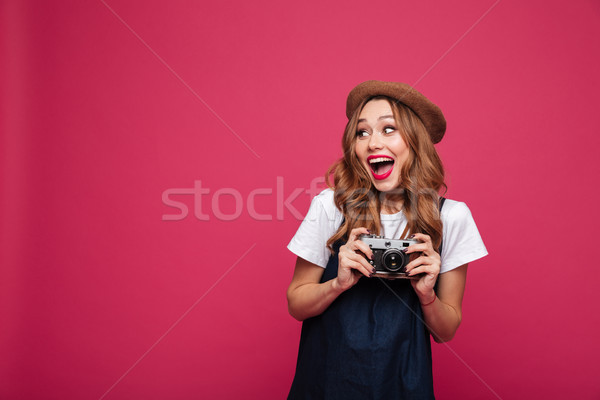 Happy amazed lady holding retro camera and looking camera isolated Stock photo © deandrobot