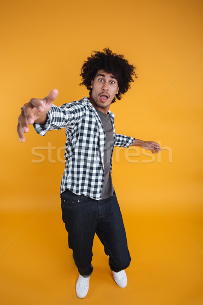 Full length portrait of a surprised astonished african man Stock photo © deandrobot