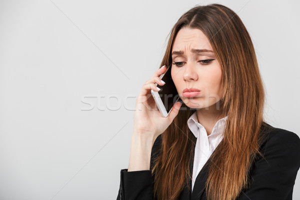 Sad woman talking on smartphone isolated Stock photo © deandrobot