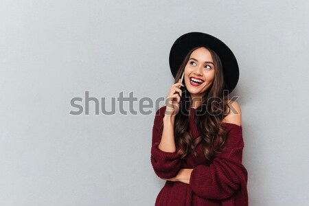 Side view of Pleased brunette woman in sweater listening music Stock photo © deandrobot