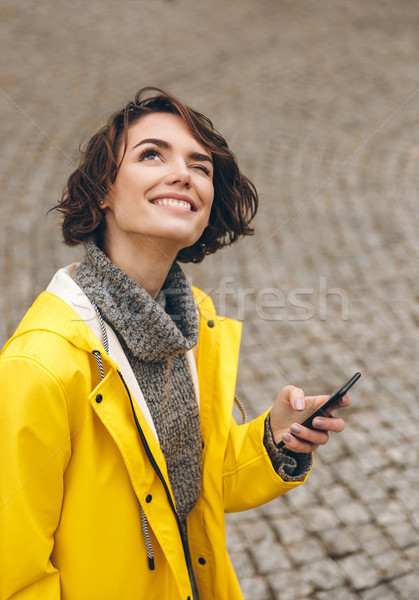 Curious woman with curly brown hair reading forecast in smartpho Stock photo © deandrobot