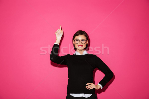 Pretty smiling lady pointing up at copy space isolated Stock photo © deandrobot